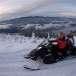 backcountry snowmobiling with a river in the background